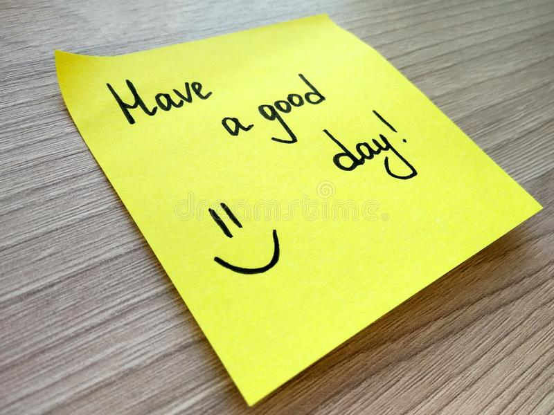 Have a good day handwritten message on yellow sticky note on wooden background. Have a good day handwritten message on yellow sticky note on wooden table royalty free stock photos