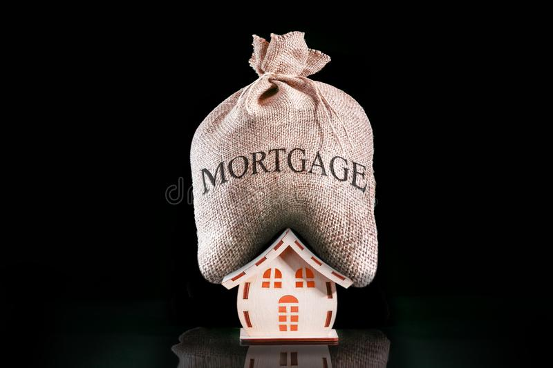 Have Heavy Home Loan. Bag with money for mortgage. Mortgage pressure on house royalty free stock photography