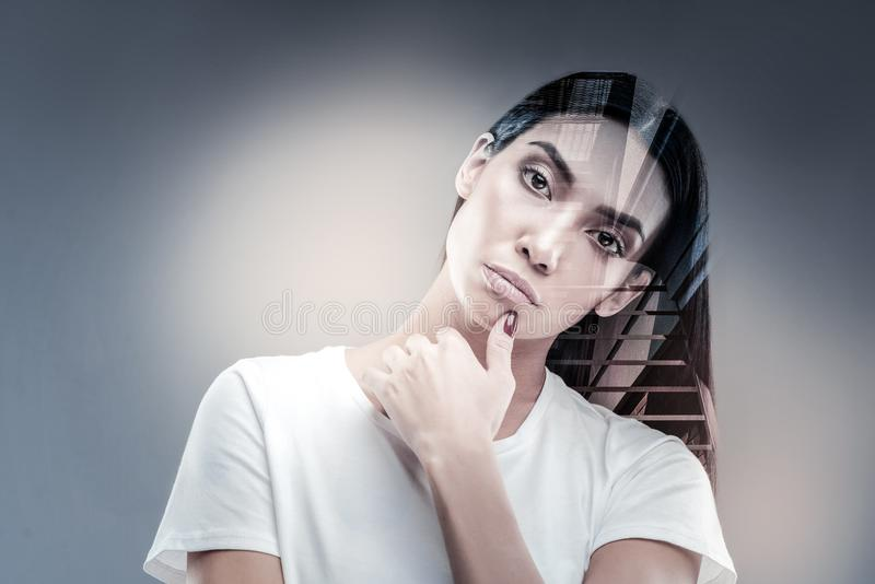 Confident young woman being deep in thoughts. Have a look. Attractive brunette raising hand while touching chin and looking at camera stock photo