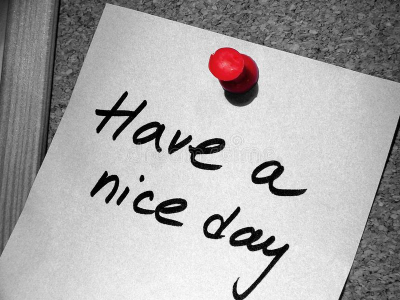 Have a nice day. A Have a nice day tag with a red pin on the cork message board stock photo