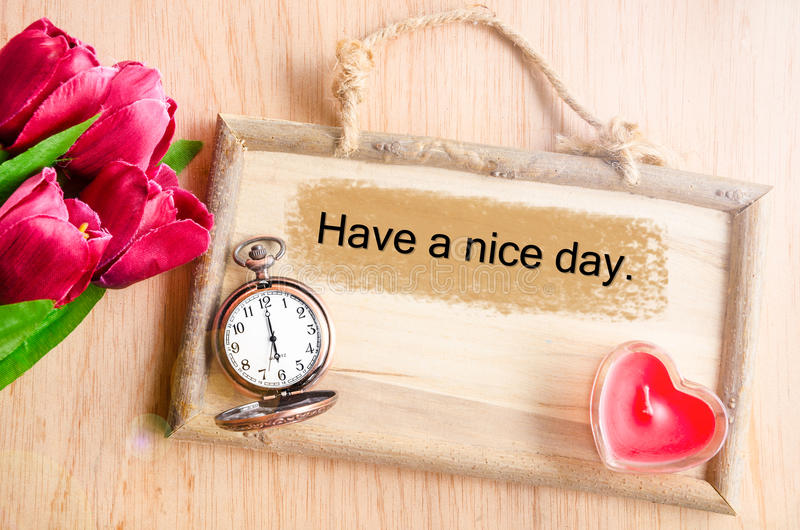 Have a nice day. Clock and red tulip with red candle heart shape on wooden background stock image