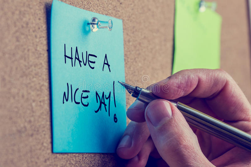 Have a nice day. Closeup of male hand writing Have a nice day message on a blue post it paper pinned to a cork bulletin board, toned retro or instagram effect stock photos