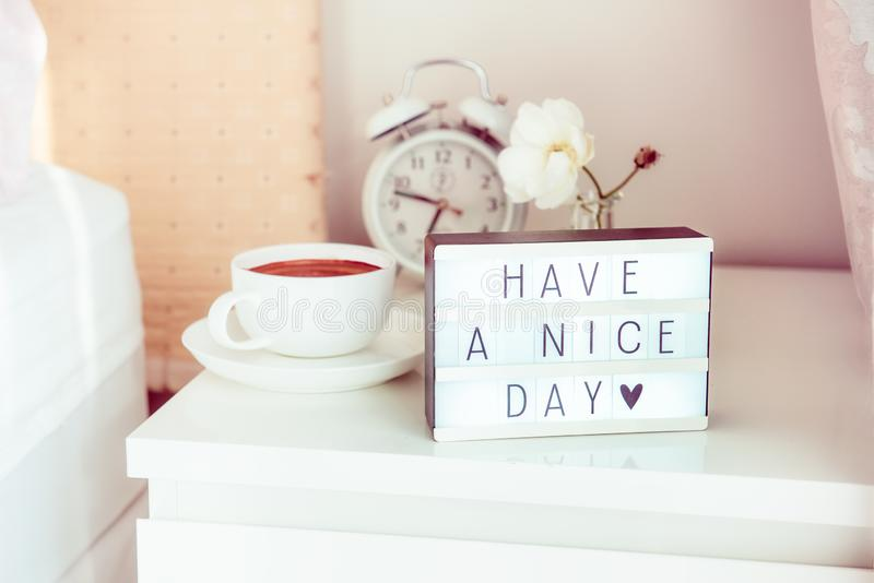 Have a nice day message on lighted box, alarm clock, cup of coffee and flower on the bedside table in sun light. Good morning mood. Hospitality, care, service royalty free stock image