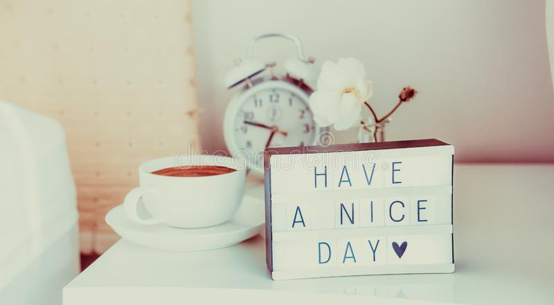 Have a nice day message on lighted box, alarm clock, cup of coffee and flower on the bedside table in sun light. Good morning mood royalty free stock photography