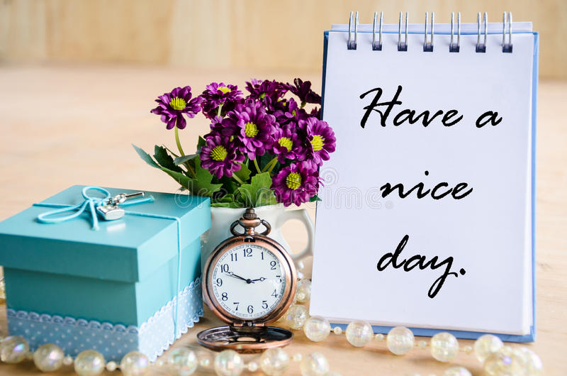 Have a nice day. Open diary, pocket watch, gift box and flower on wooden backgroudn royalty free stock photos