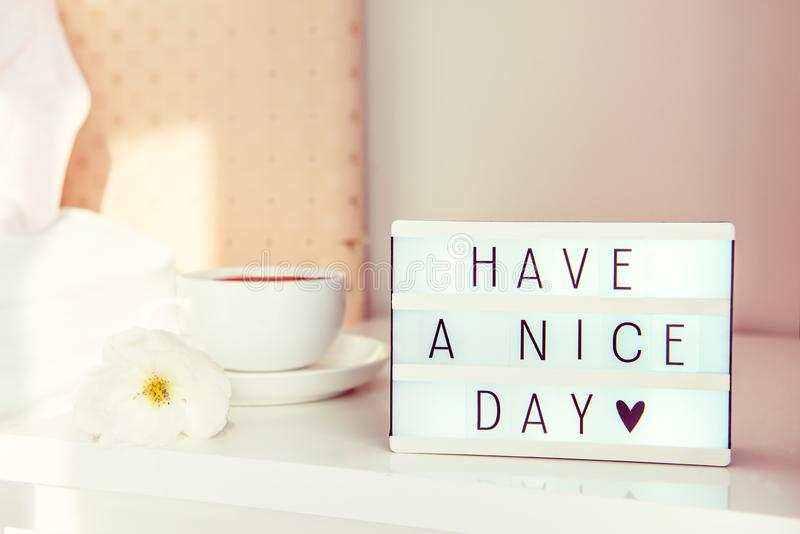 Have a nice day text message on lighted box, cup of coffee and white flower on the bedside table in sun light. Good morning mood. Hospitality, care, service stock photography