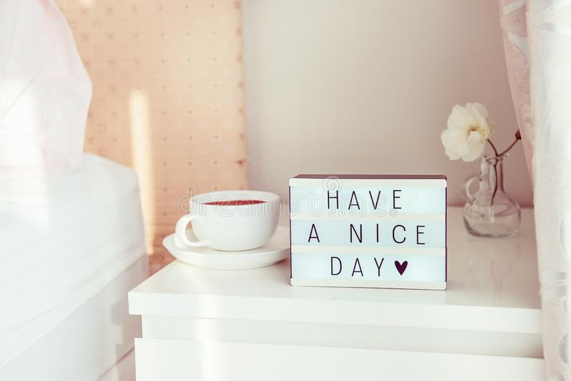 Have a nice day text message on lighted box, cup of coffee and white flower on the bedside table in sun light. Good morning mood. Hospitality, care, service stock image