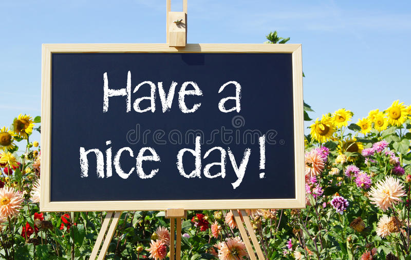 Have a nice day!. Text 'Have a nice day!' in white letters on a black chalk board supported by a wooden easel placed in a garden of colorful summer flowers and stock image