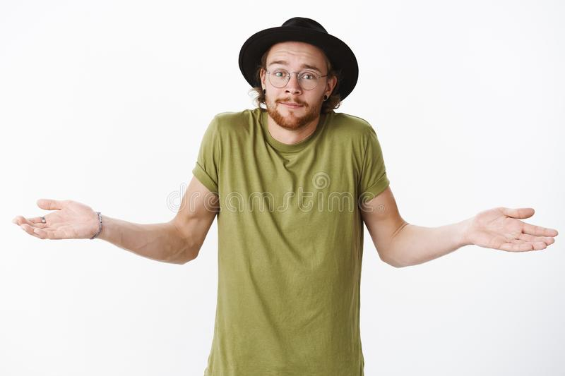 Have no idea what talking about. Confused unsure handsome young bearded male in hat and glasses smirking uncertain as stock photos