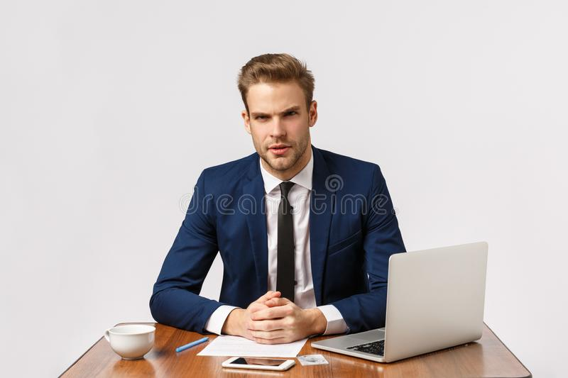 We have serious meeting here. Focused smart successful businessman, lawyer sitting office lean on desk and looking royalty free stock photography