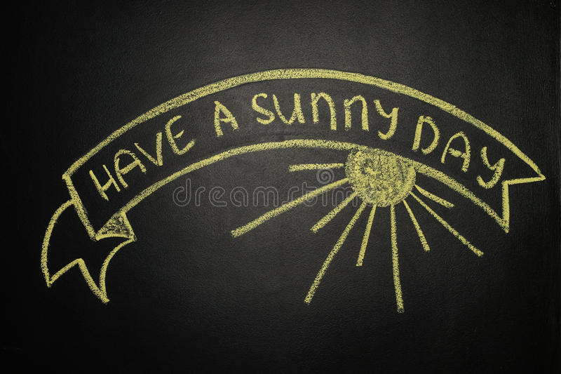 Have a sunny day with Ribbon Banner, written with chalk on a blackboard stock photo