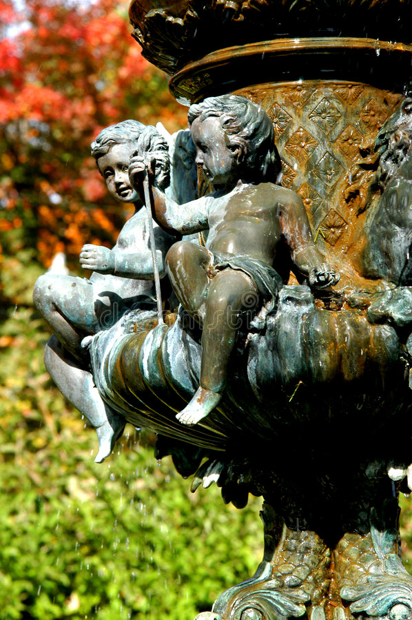 Have you been here long?. Statue of two cherub children look toward each other. Intricately carved and framed by a Fall sunny day. They sit on a waterfountain in royalty free stock photography