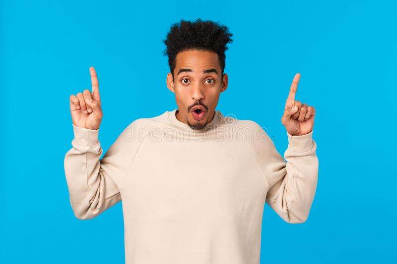 Have you seen it. Attractive impressed african-american guy with moustache, afro haircut, saying wow, telling about. Event, product advertising, pointing royalty free stock photos