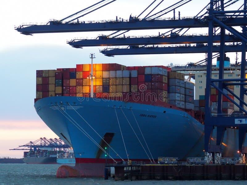 Haven van Felixstowe, Suffolk, het UK, 11 Februari 2018: Kranen die containers op een vrachtschip laden bij schemer stock afbeeldingen