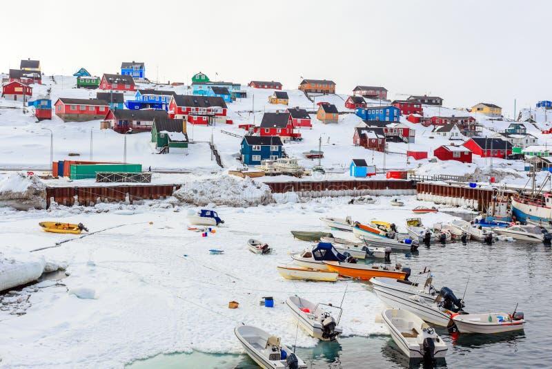 Havengebied met motorboten en kleurrijke inuithuizen in backgroung, Aasiaat-stad stock afbeeldingen