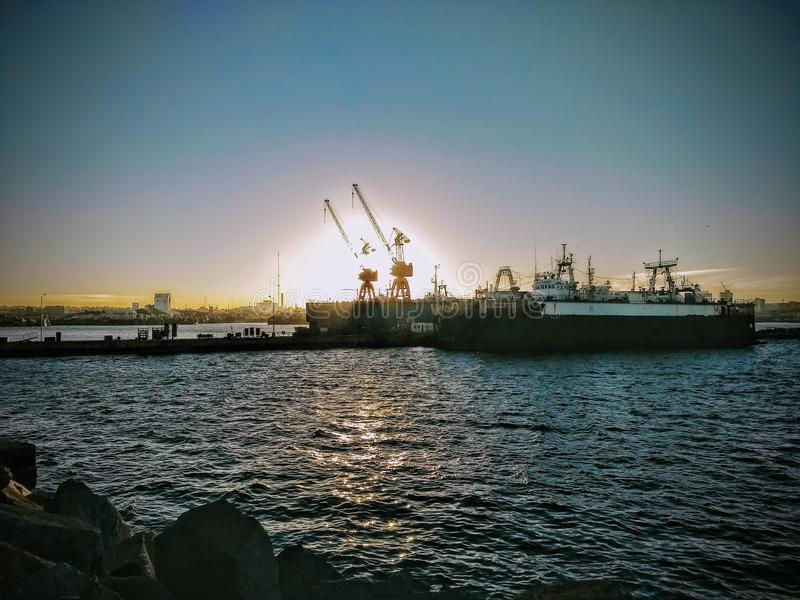 Havenmachines in zonsondergang stock fotografie