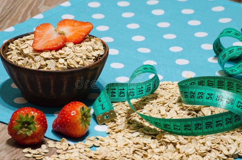 Havermeel, aardbeien in een glaskom en het meten van band royalty-vrije stock foto's