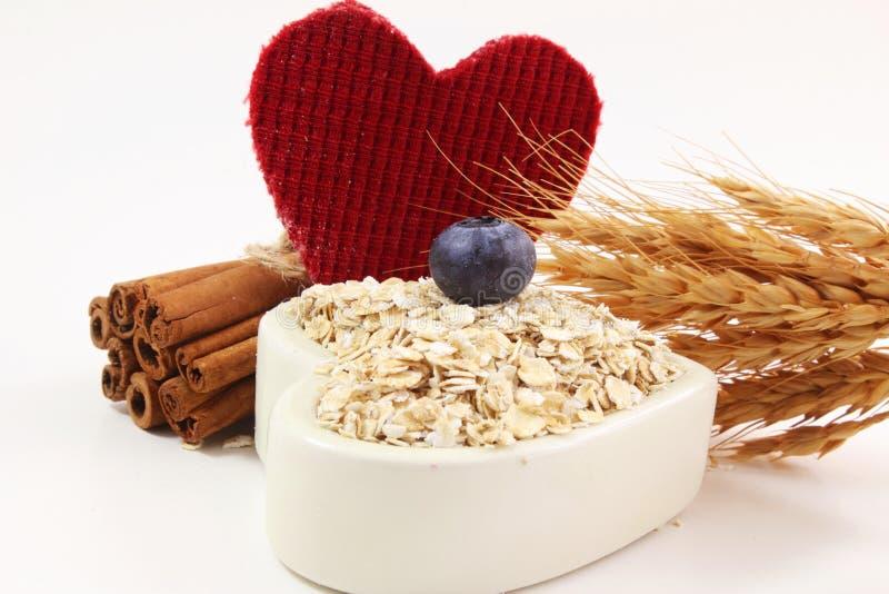 Havermeel in de kom van de hartvorm met van de bosbessenkaneel en haver oren op witte achtergrond stock foto