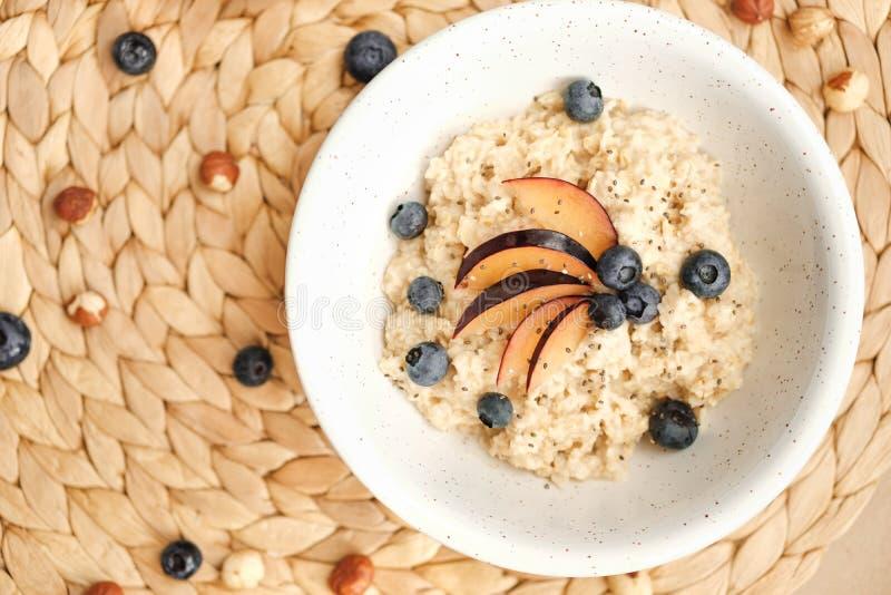 Havermeel in een kom met noten, bosbessen, pruimen en chiazaden - gezond veganistontbijt royalty-vrije stock fotografie