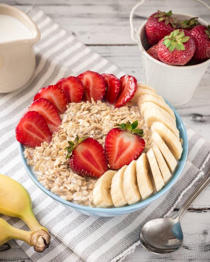 Havermeel in kom met aardbeien en bananen royalty-vrije stock afbeelding