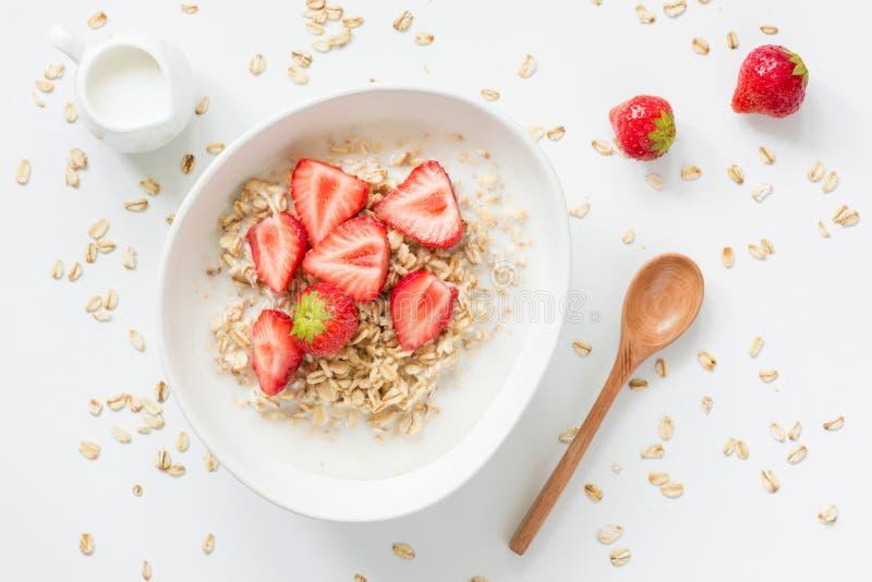 Havermeelhavermoutpap met aardbeien en melk in kom royalty-vrije stock foto's