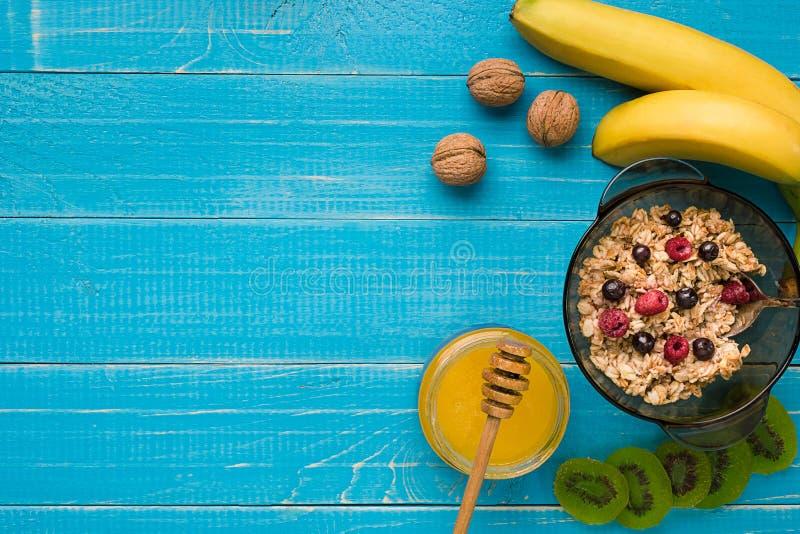 Havermeelhavermoutpap met banaan, kiwifruit, noten en honing in een kom met ei voor gezond ontbijt op rustieke houten royalty-vrije stock afbeeldingen