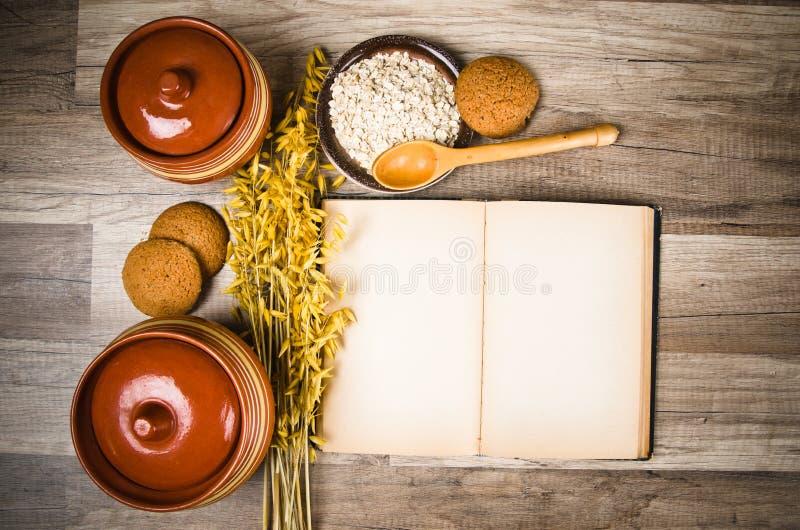 Havermeelkoekjes en een oud receptenboek royalty-vrije stock foto