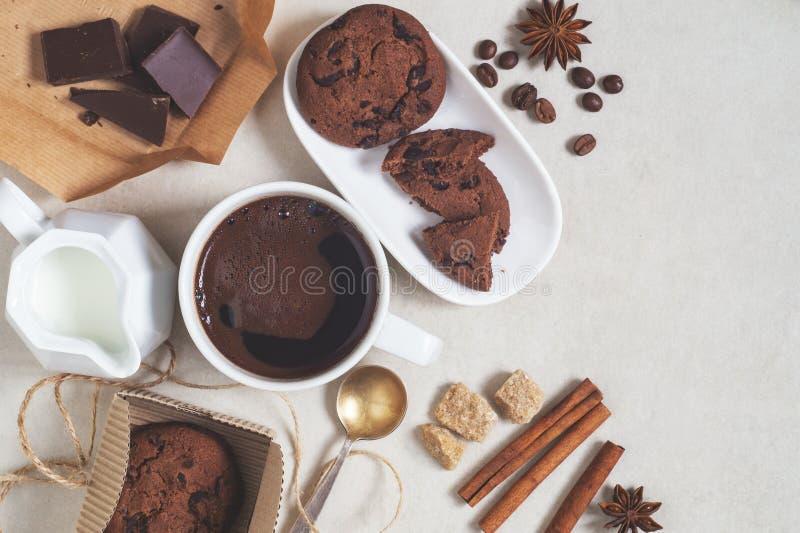 Havermeelkoekjes met cacao en chocolade, kop van koffie en een melkkruik royalty-vrije stock fotografie