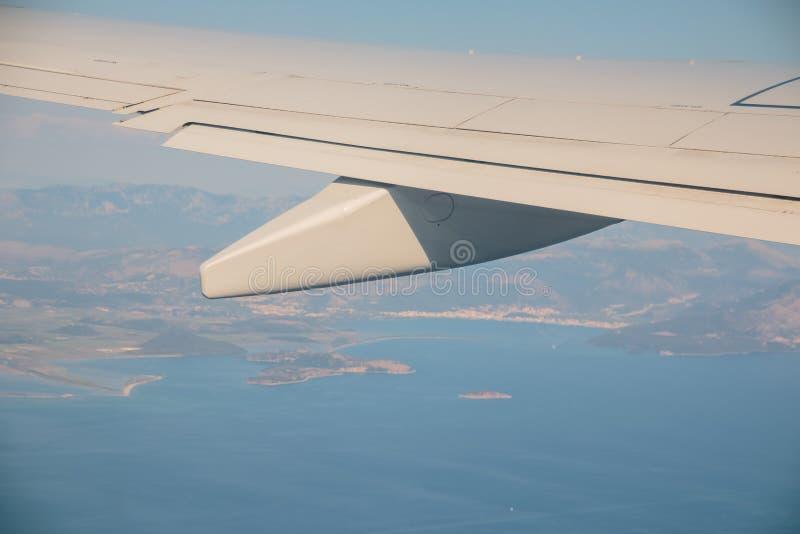 Havet och ön såg ut ur det plana fönstret med vingflygplan Härlig blå havs- och landskapsikt från fotografering för bildbyråer