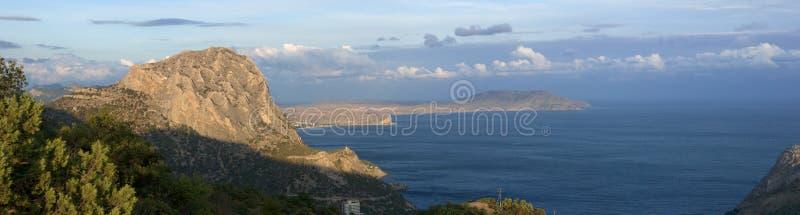 Havet seglar utmed kusten med berg arkivbilder