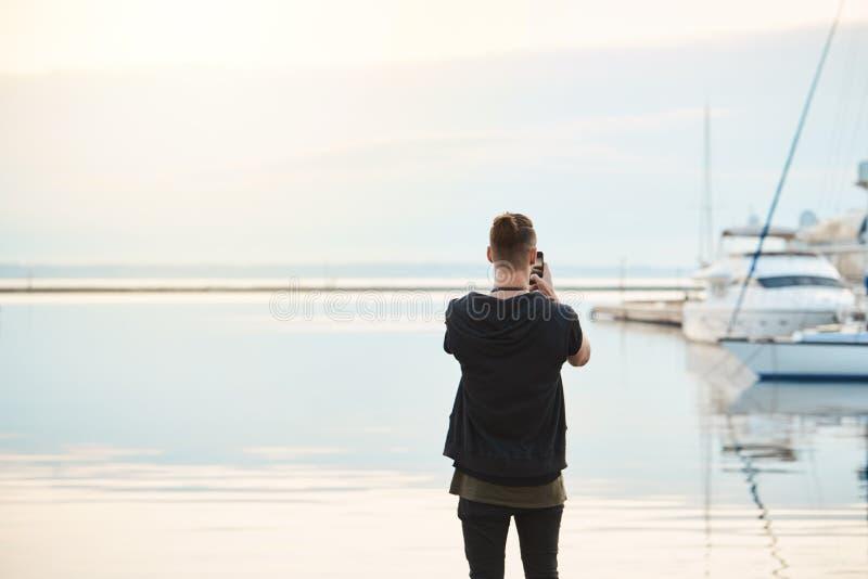 Havet tar din andedräktawat Tillbaka siktsskott av den stilfulla unga europeiska grabben i moderiktig kläder som står på att ta f royaltyfri foto
