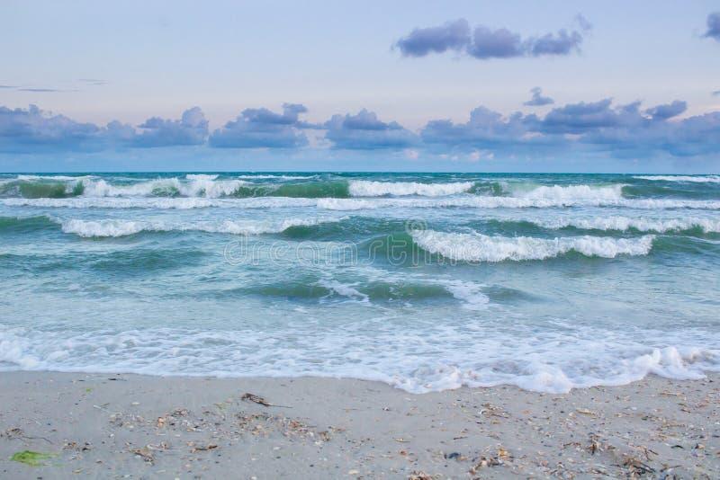 Havet vinkar rullningen på den tomma stranden, stormig molnig soluppgång arkivbild