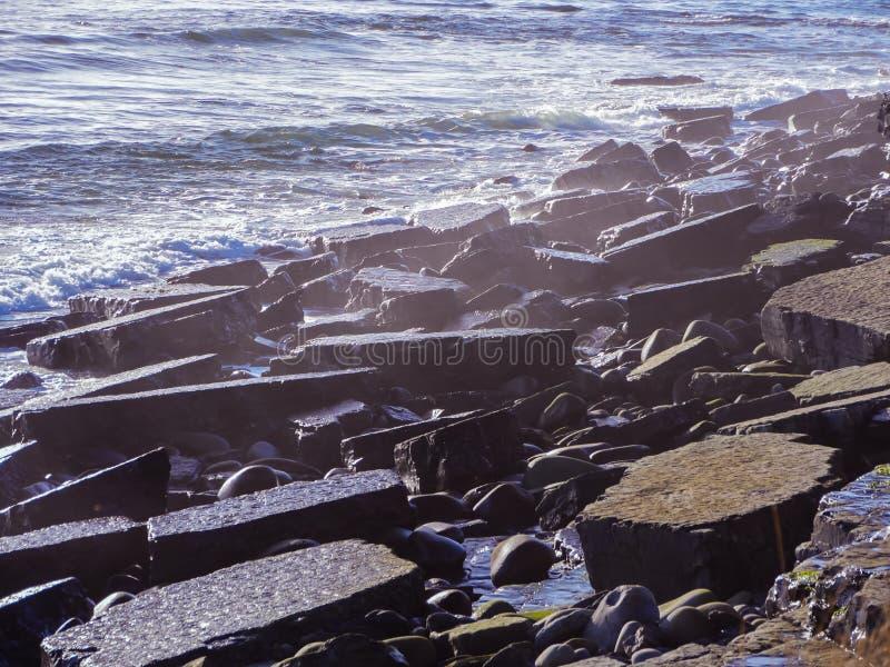 Havet vinkar snärten fodrar får effekt vaggar på stranden royaltyfri bild