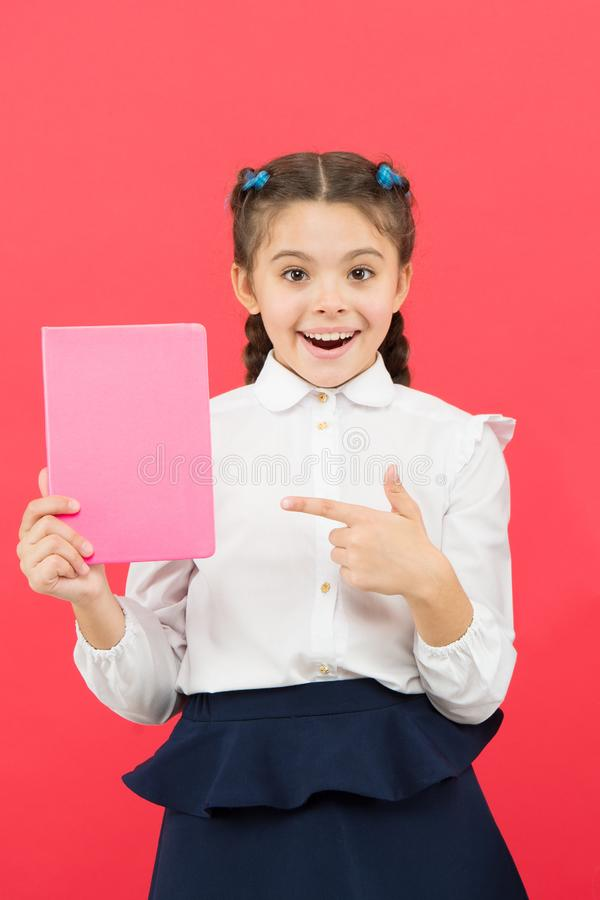 Having access to information through books. Small child got information on red background. Little girl pointing finger. At book for information. Spread royalty free stock photo