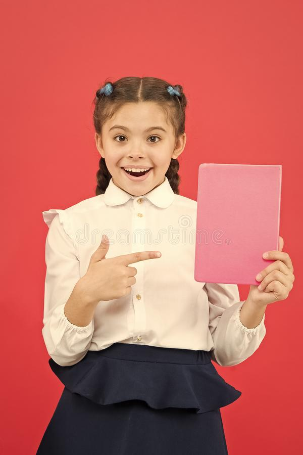 Having access to information through books. Small child got information on red background. Little girl pointing finger. At book for information. Spread royalty free stock image