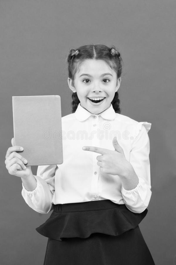 Having access to information through books. Small child got information on red background. Little girl pointing finger. At book for information. Spread stock image