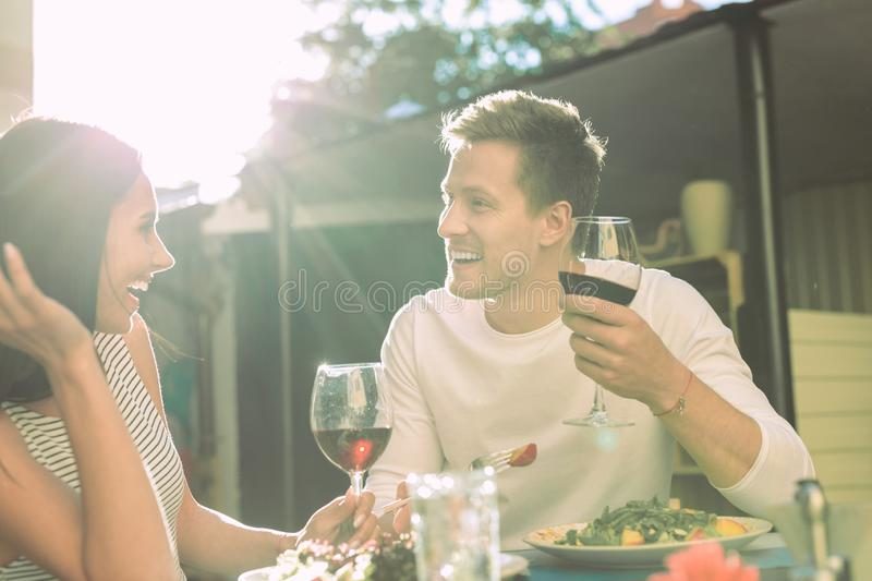 Laughing short-haired man in white top telling jokes while dating. Having active conversation. Laughing short-haired men in white top telling jokes while dating stock images