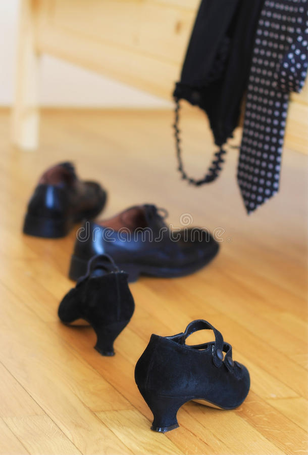 Having an affair. Making love, having partnership concept; woman heels and dress, man shoes and tie in the bedroom royalty free stock photography
