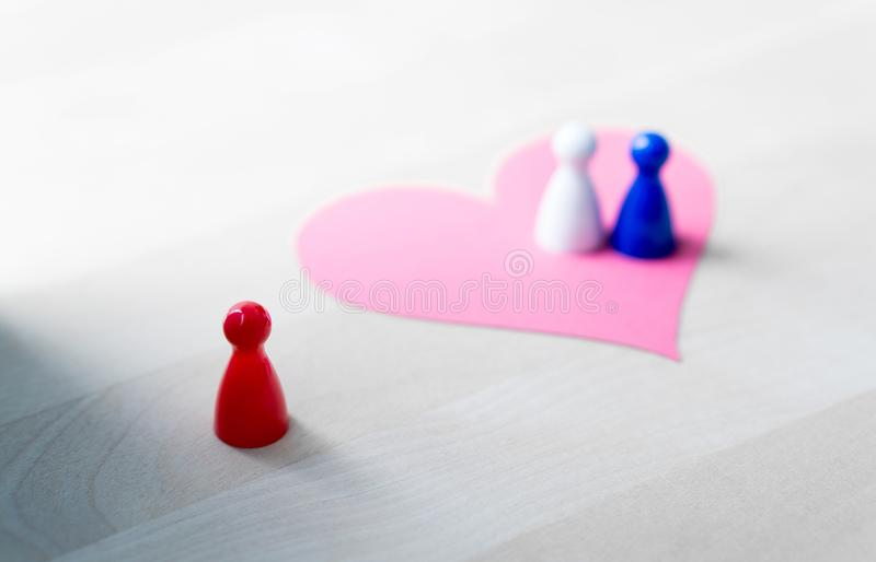 Having affair, infidelity or cheating concept. Love triangle or being third wheel. Board game pawns and paper heart on table royalty free stock image