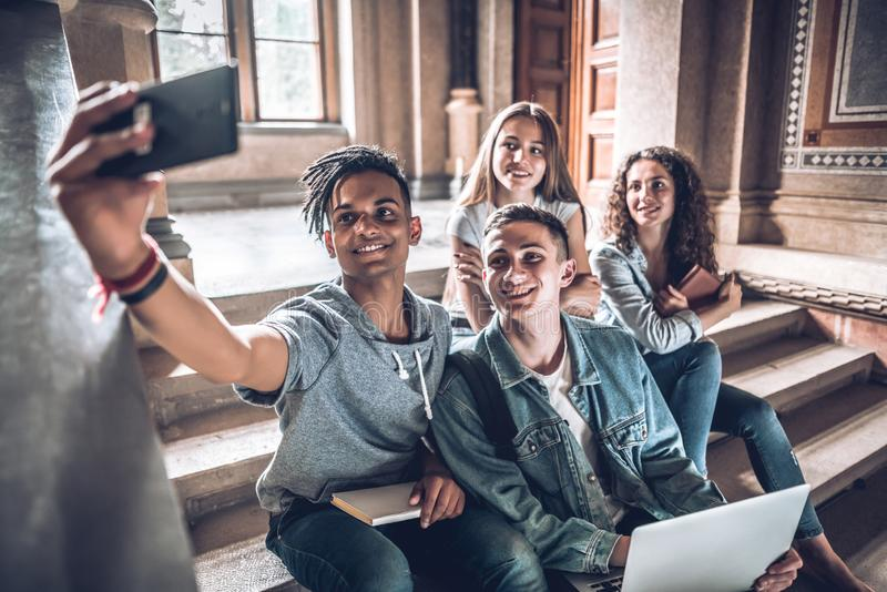 Having the best time with friends. Group of students studying while sitting on stairs in university and making selfie on smart royalty free stock image