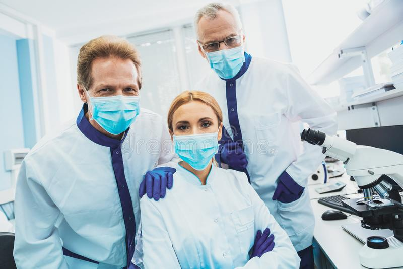Group of scientists posing on camera. Having break. Professional researchers sitting at their workplace while being satisfied with work royalty free stock photo