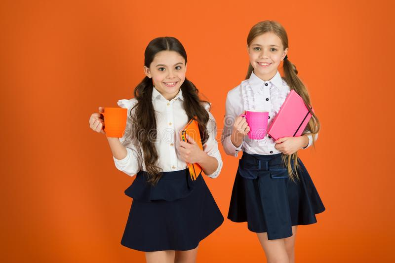 Having break relax. Drinking tea while break. School mates relaxing with drink. Enjoy being pupil. Girls kids school. Uniform orange background. Schoolgirl hold royalty free stock photos