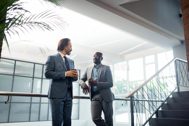 Bearded businessman speaking with partner and having coffee time royalty free stock image