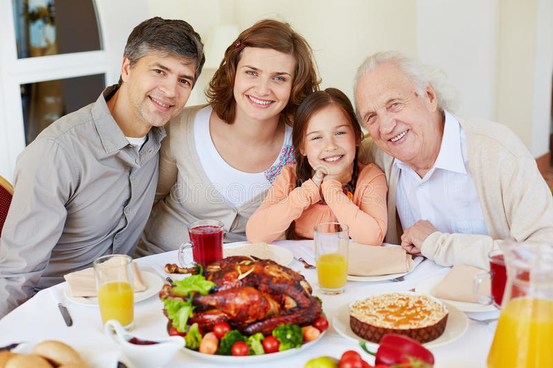 Having dinner together. Portrait of family of four sitting at celebration table stock photography