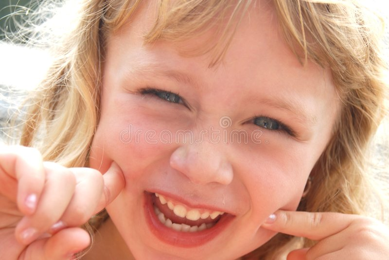 Having Fun. Cute girl making a funny smiling face for the camera royalty free stock photos