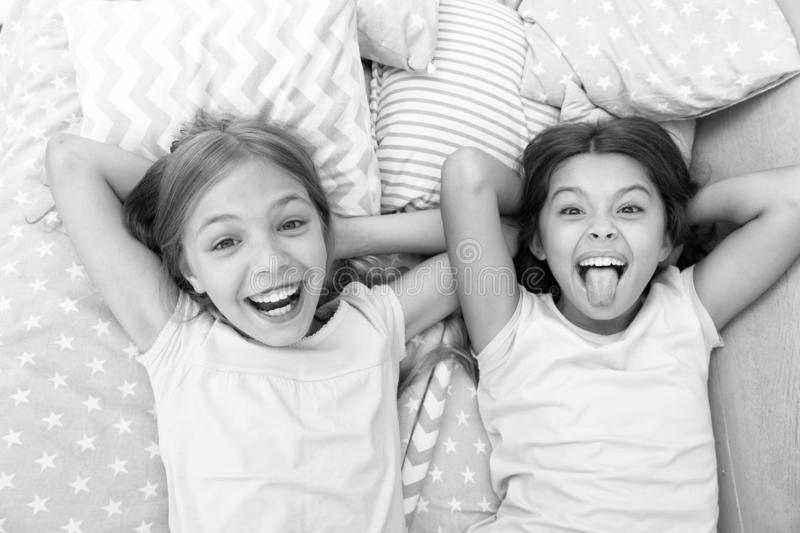 Having fun with best friend. Children playful cheerful mood having fun together. Pajama party and friendship. Sisters. Happy small kids relaxing in bedroom royalty free stock images