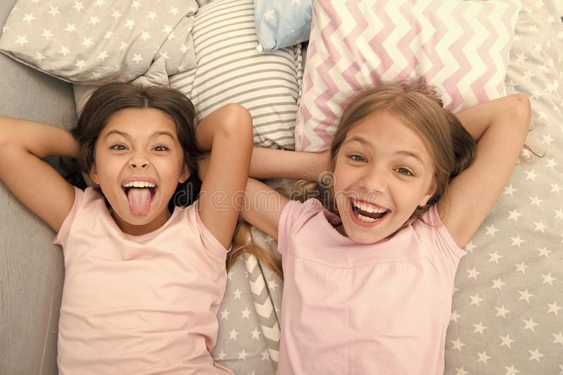 Having fun with best friend. Children playful cheerful mood having fun together. Pajama party and friendship. Sisters. Happy small kids relaxing in bedroom royalty free stock photos