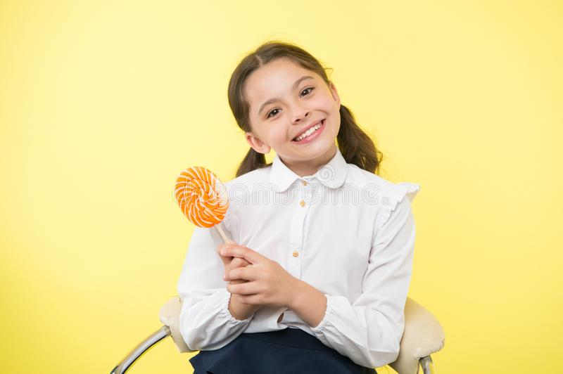 Having fun with candy. Girl cute kid ponytails hairstyle eat sweet lollipop. Sweets in appropriate portions ok. Girl. Pupil school uniform likes sweet lollipop stock images