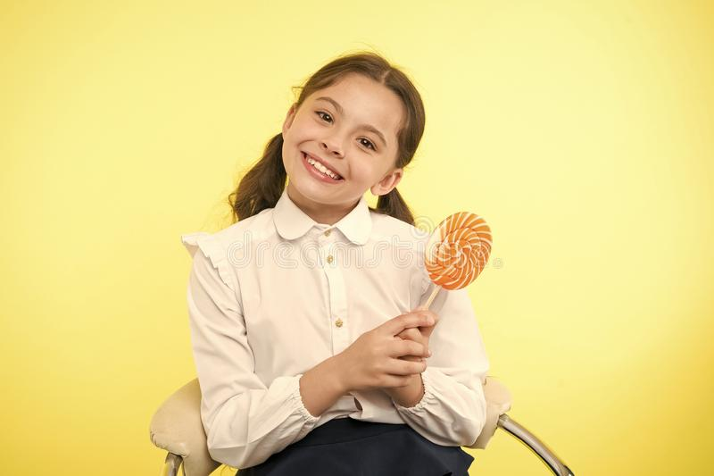 Having fun with candy. Girl cute kid ponytails hairstyle eat sweet lollipop. Sweets in appropriate portions ok. Girl. Pupil school uniform likes sweet lollipop royalty free stock photos