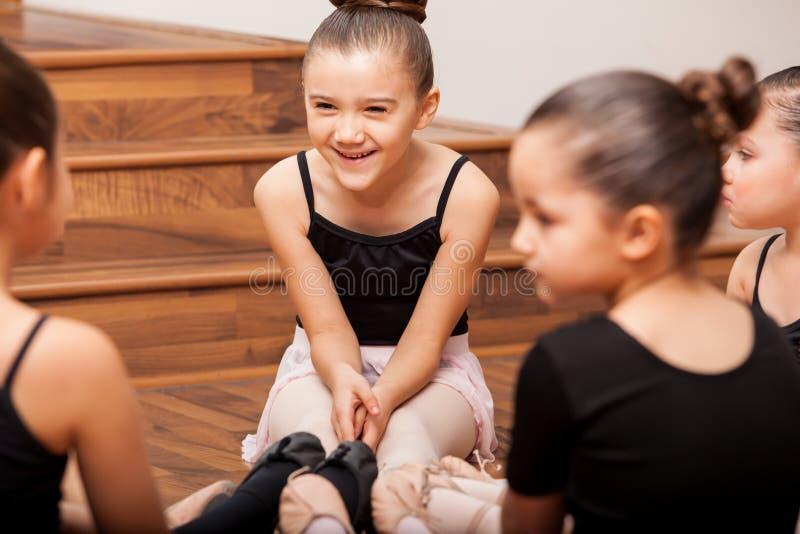 Having fun during dance class. Happy little girl having fun with her friends during dance class in a dance academy stock photo
